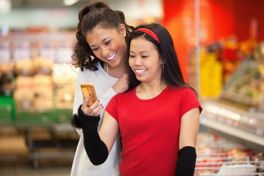 Smiling young women using mobile phone in shopping centre