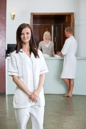 Young Caucasian woman with people in background at spa centre