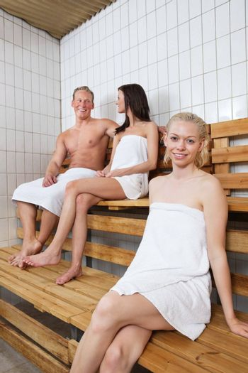 Group of people sitting on bench in a sauna