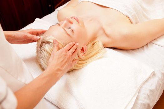A pretty young woman receiving a scalp massage in a spa