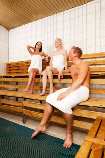 A group of friends laughing and talking in a sauna