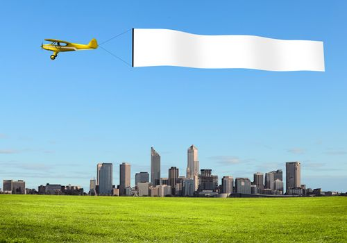 Plane in the sky above the city with blank flag