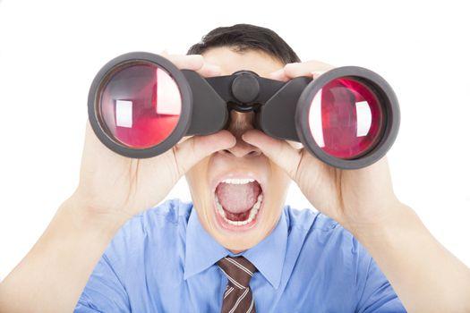 surprised businessman looks through binoculars and isolated