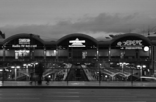 Side view of the Mainz main station in the evening. A man with walker walks through the focus.