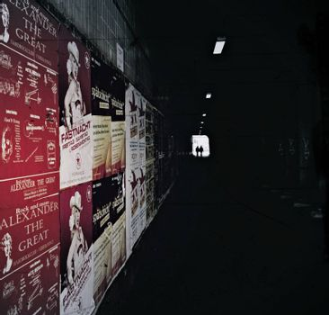 under a bridge, the walls are covered with posters and in the distance walks a pair.