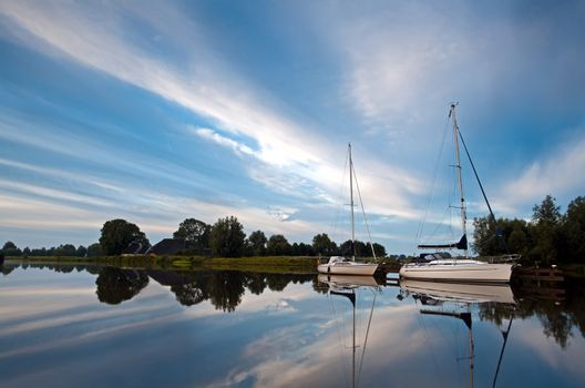 two white yachts and sky reflections