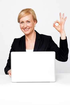 Happy businesswoman gesturing okay sign