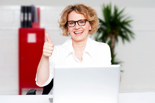 Successful businesswoman gesturing thumbs up