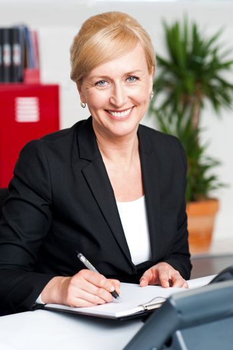 Female secretary writing on notepad