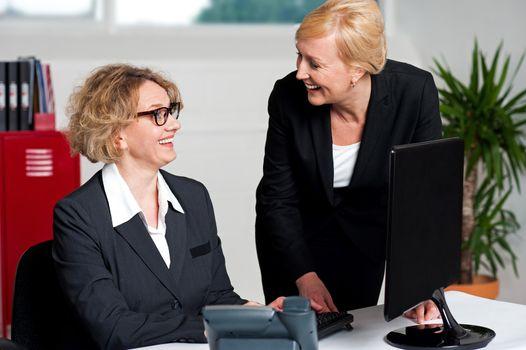 Joyful businesswomen enjoying at work desk