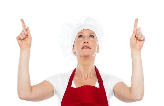 Female chef in uniform pointing upwards