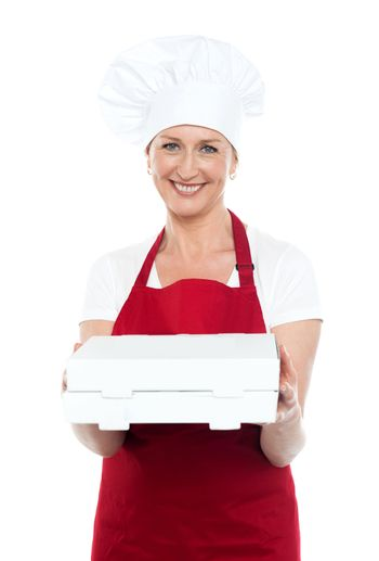 Female baker presenting pizza to you in a box