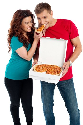 Girl sharing a pizza piece with her boyfriend