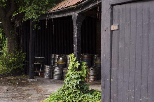A cache of metal beer barrels in a pub porch