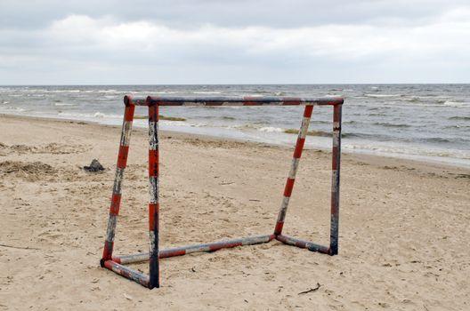 Steel metal football goal gate on sea sand. Active recreation on beach seaside.