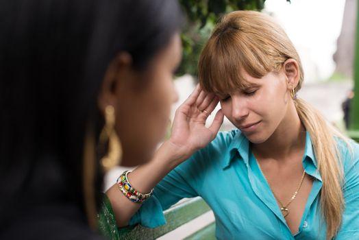 Woman having headache while talking with friend
