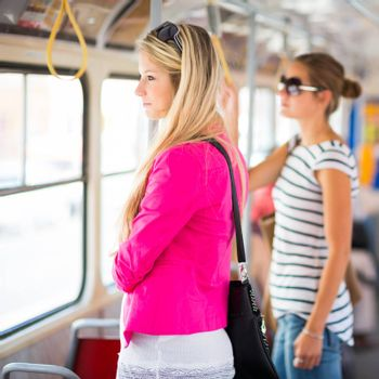 Pretty, young woman on a streetcar/tramway, during her commute to work (color toned image; shallow DOF)