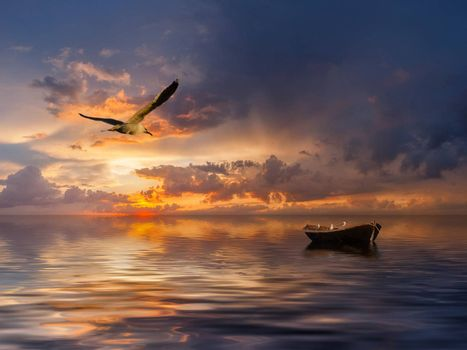 Beautiful landscape with lonely boat and birds against a sunset, majestic clouds in the sky
