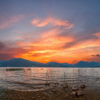 Colorful sunrise on Lake with majestic clouds, Alpes mountains on background