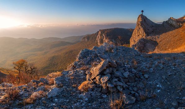 A man standing at mountain top with camera against a beautiful sunrise