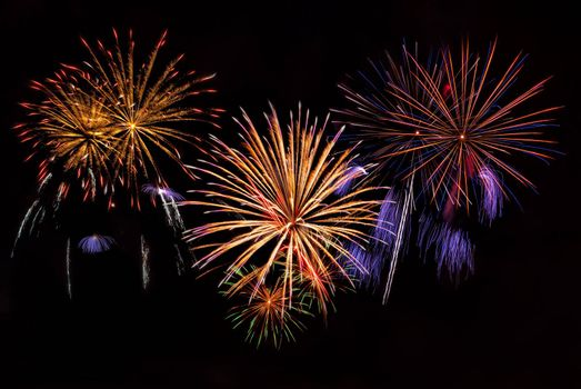 Beautiful colorful holiday fireworks on the night sky background, long exposure