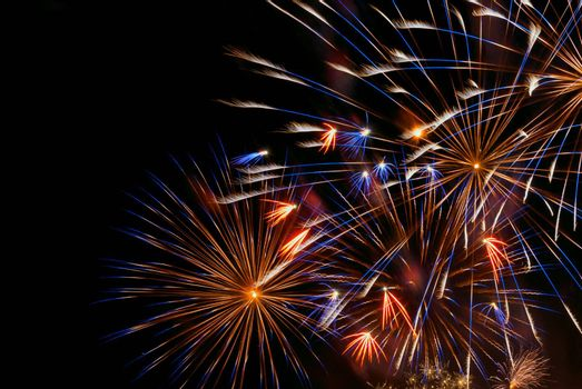 Beautiful colorful holiday fireworks on the black sky background, close-up, long exposure