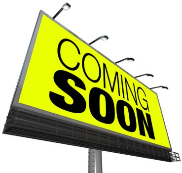 The words Coming Soon on a large outdoor billboard on a yellow background advertises a new store, grand opening, sneak preview of a movie or feature or other event, product or object