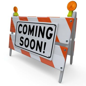 An orange and white construction barricade sign with the words Coming Soon to announce and introduce or give a sneak preview of a new feature, road project, business, event or other object