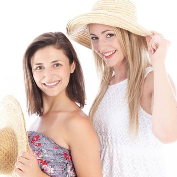 Happy female friends enjoying the summer in their casual sleeveless dresses and straw sunhats Happy female friends enjoying the summer in their casual sleevelss dresses and straw sunhats