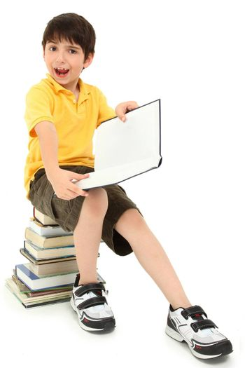 Adorable elementary age school boy child making faces on stack of books.