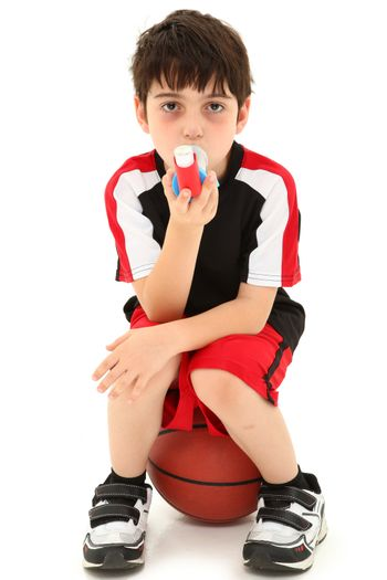 Boy Child with exercise or sport induced asthma attack sitting on basketball over white.