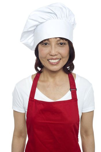 Young smiling female chef wearing red apron