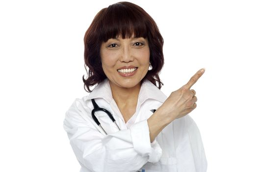 Matured surgeon pointing at the copy space