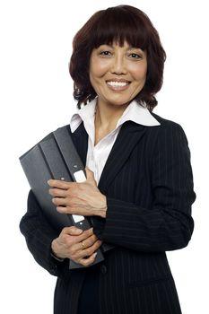 Smiling female executive holding binder