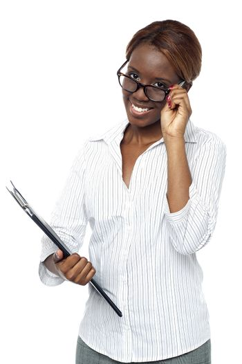 Businesswoman holding file and adjusting her spectacles