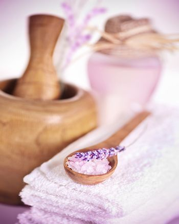 Image of spa accessories, white soft towel, wooden mortar, herbal oil, spoon with sea salt and lavender flower on massage table, toiletries, natural cosmetics, aromatherapy, beauty and health care