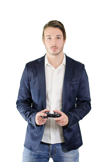 Young man standing, with videogame joypad in his hands