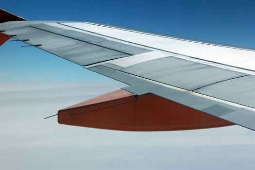 The wing of an aeroplane with orange parts in the sky