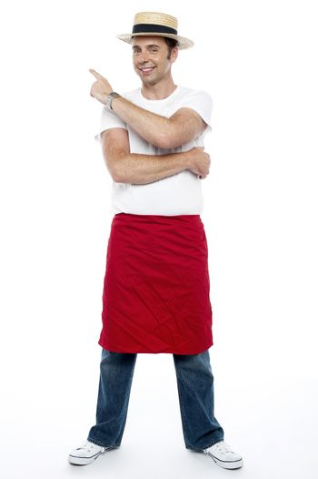 Man wearing a hat and apron pointing away