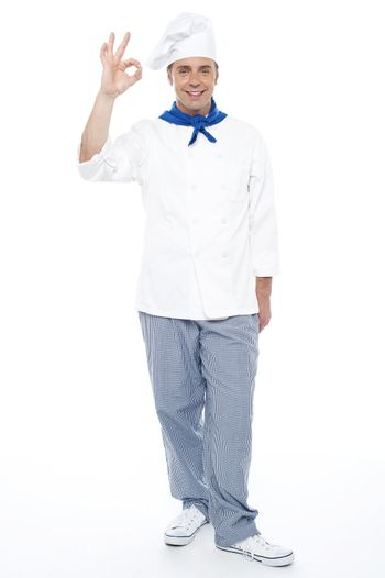 Full length portrait of chef showing okay sign