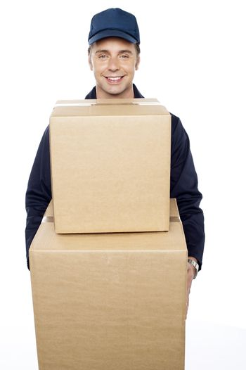 Young man carrying huge cardboard boxes