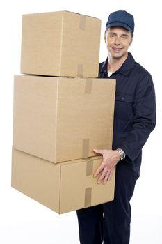Working man delivering stack of cardboard boxes