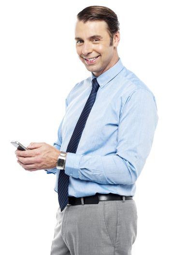 Smiling young manger sending sms from phone