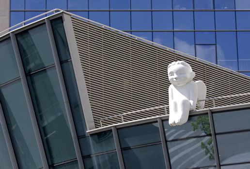 Statue of white angel sitting on the roof of the modern building