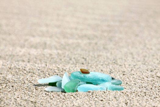 A pile of sea glass pebbles on the sand