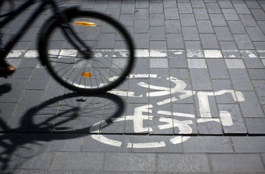 Bicycle route sign on the street and motion blured bicycle wheel