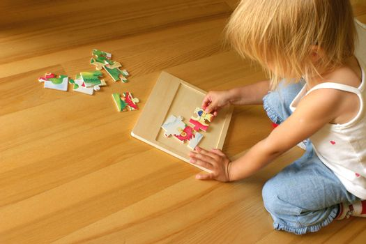 2-3 years old girl kneeling on the floor and solving jigsaw puzzle