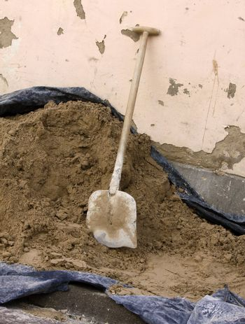 Vertical picture of dirty shovel put in the heap of concrete