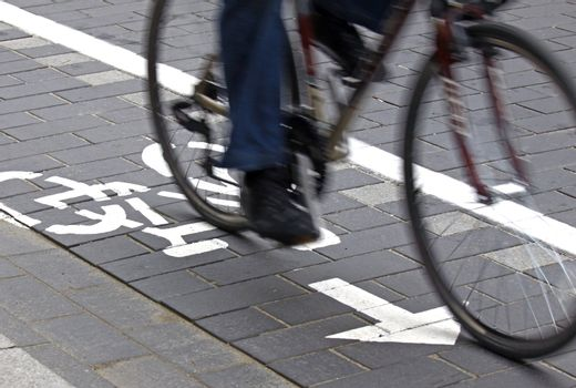Intentionally blurred bicycle on the pavement with painted cycling signs