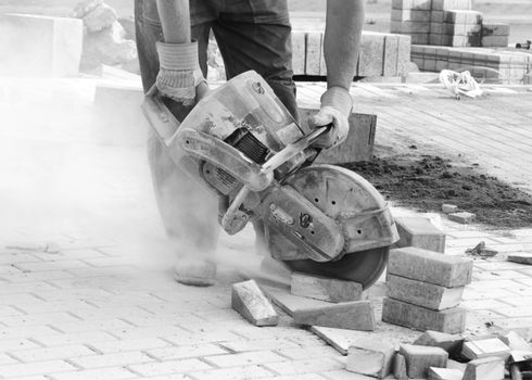 Black and white picture of worker with concrete saw in his hands and working